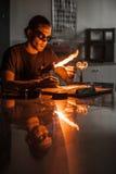 Glassblowing młody człowiek Pracuje na pochodnia płomieniu z Szklanymi tubkami fotografia royalty free