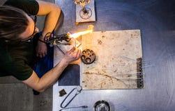 Glassblowing młody człowiek Pracuje na pochodnia płomieniu z Szklanymi tubkami obraz stock
