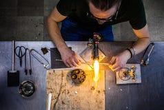Glassblowing młody człowiek Pracuje na pochodnia płomieniu z Szklanymi tubkami zdjęcie royalty free