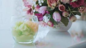 Glasschüssel mit buntem scheuern sich inner und Blumen auf dem Hintergrund am Badekurortsalon stock video footage