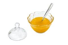 Glasschüssel mit Honig und silbernem Löffel Lizenzfreie Stockfotografie