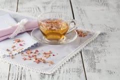 Glasschale mit frischem grünem Tee und trockenen Rosen Stockfoto
