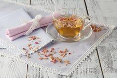 Glasschale mit frischem grünem Tee und trockenen Rosen Stockbild