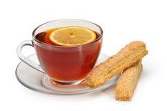 Glasschale mit Tee und einer Zitrone auf einer Glasuntertasse und Plätzchen Lizenzfreies Stockbild