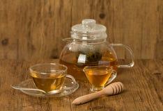 Glasschale und Teekanne mit grünem Tee mit Honig Stockfoto