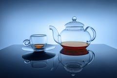 Glasschale und Teekanne mit kleiner Menge Tee Lizenzfreies Stockbild