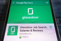 Glassdoor在谷歌戏剧在智能手机显示的商店网站上的工作查找应用程序掩藏在牛仔裤装在口袋里 库存图片