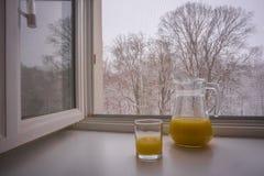 glasse和水罐风景看法部分填满用橙汁 库存照片