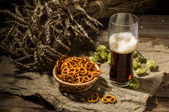 Glasse beer with wheat and hops, basket of pretzels Royalty Free Stock Photography