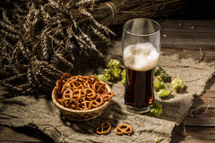 Glasse beer with wheat and hops, basket of pretzels Royalty Free Stock Images