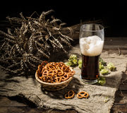 Glasse beer with wheat and hops, basket of pretzels Stock Photography