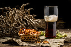 Glasse beer with wheat and hops, basket of pretzels Stock Photos