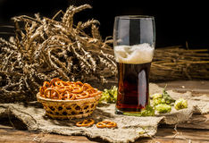 Glasse beer with wheat and hops, basket of pretzels Royalty Free Stock Image