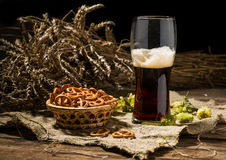 Glasse beer with wheat and hops, basket of pretzels Stock Images