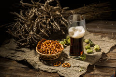 Glasse beer with wheat and hops, basket of pretzels Royalty Free Stock Photos