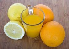 Glasse des Orangensaftes und der Früchte Stockbild