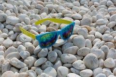 Glasse di Sun sulle pietre Immagine Stock