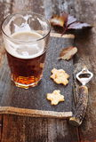 Glasse of light beer, crackers and beer bottle opener Stock Images