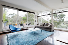 Glassed wall scandinavian styled living room with amazing views. Glassed wall Australian living room with amazing views of bush treetops Royalty Free Stock Photos