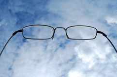 Glasses. Reading glasses against cloudy sky Royalty Free Stock Images