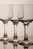 Glasses. Three elegant wine bottles siting on a table Stock Images