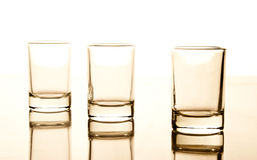 Glasses. Three little glasses and their reflection isolated on a white background Royalty Free Stock Photos