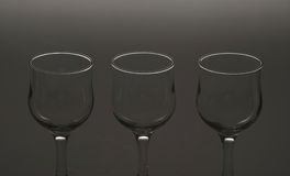 Glasses. The fine contour of three wine glasses on a grey background Royalty Free Stock Photography