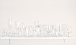 Glasses. Different types of glasses on one shalf Royalty Free Stock Photos