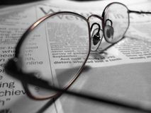 Glasses. On newspaper, selective colour stock images