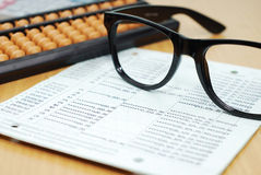 Glasses and abacus on bank account. Business concept Stock Photos