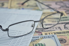 Glasses and account book on dollar bank note stock photos
