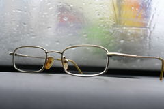 Glasses against the wet glass. Lying on the car panel Stock Images