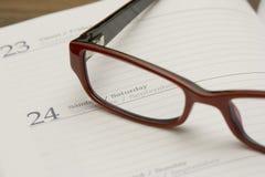 Glasses on agenda. Pair of woman office glasses left on an agenda Stock Photo