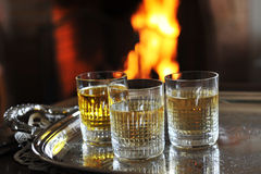 Glasses and alcohol. Close-up of glasses with alcohol in front of fireplace Royalty Free Stock Image