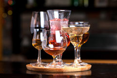 Glasses with alcohol. Glasses of alcohol on a wooden plate stock photos