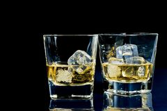 Glasses of alcoholic drink with ice on blue light Royalty Free Stock Photo