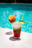 Glasses of Aperol Spritz and Mojito Royal cocktails. Two glasses of Aperol Spritz and Mojito Royal cocktails on the swimming pool nosing Royalty Free Stock Images