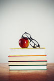 Book lover. Glasses and apple on a pile of books royalty free stock photos