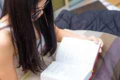 Glasses asian woman reading a book on bed. At home Stock Photography