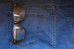 Glasses in back blue jeans. Pocket denim background texture Stock Images