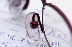 Glasses on a background of hand written mathematical calculations on a piece of paper. royalty free stock images