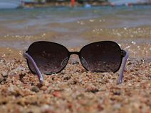 Glasses on the background of the sea. Sunglasses at the sea on the sand Royalty Free Stock Photo