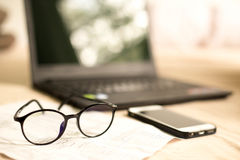 Glasses with bank statement and cell phone Royalty Free Stock Photo