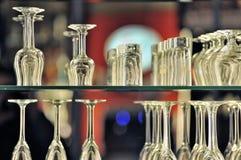 Glasses at bar. Shelves of glasses stacked up at a bar Stock Photo