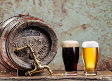 Glasses of  beer and ale barrel on the wooden table. Craft brewe Stock Photos