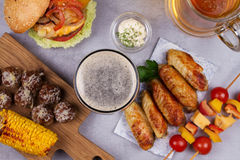 Glasses of beer with chicken wings, burger, meat balls, grilled corn and vegetables. Beer bites Stock Photos