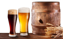 The glasses of beer near woden barrel. Royalty Free Stock Photo