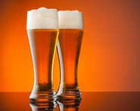 Glasses of beer with orange background Stock Photos
