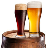 The glasses of beer over woden barrel. Stock Image