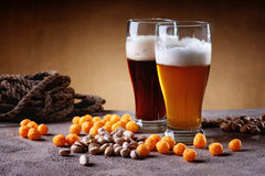 Glasses of beer, rope, cheese balls and pistachio nuts Stock Photos
